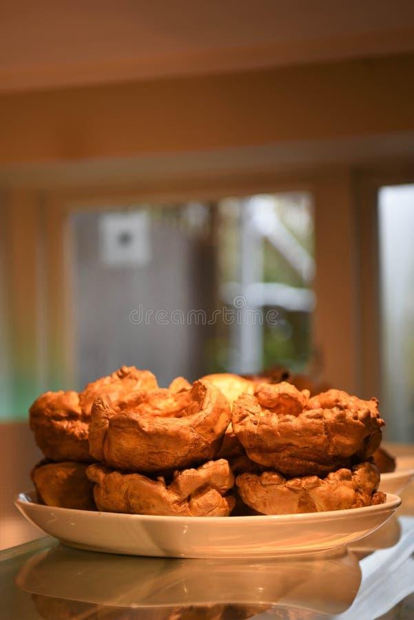 Pudins de Yorkshire dourados deliciosos para um jantar do assado foto de stock royalty free
