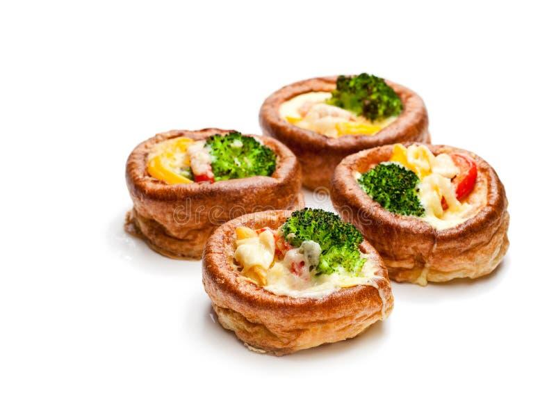 Pudins de Yorkshire enchidos com brócolis e iso dos ovos mexidos imagens de stock royalty free