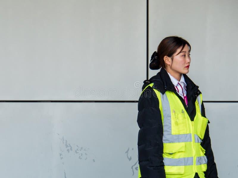 PUDONG, SHANGHAI - 13 BRENG 2019 in de war - een vrouwelijke luchthavenwerknemer bij Pudong-Luchthaven, Shanghai met exemplaarrui stock foto