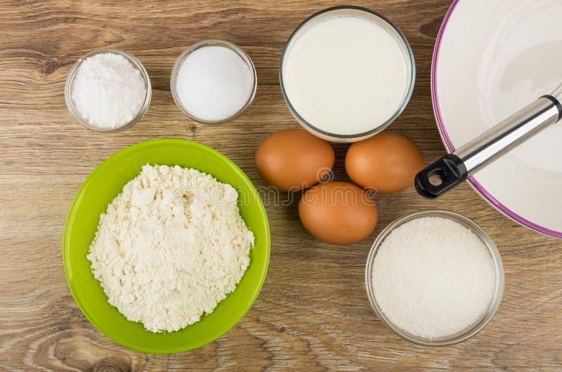Pudra i bunke, bowla, vifta och andra ingredienser för pannkakor arkivbilder