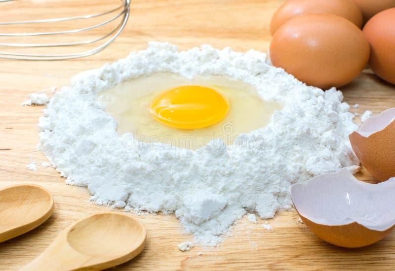 Pudra med ägget och ingredienser för hemlagat bageri på träbakgrund arkivfoto