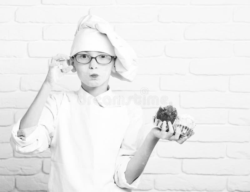 Pudrar den gulliga kockkocken för den unga pojken i den vita likformign och hatten på nedfläckad framsida med exponeringsglas som royaltyfri bild