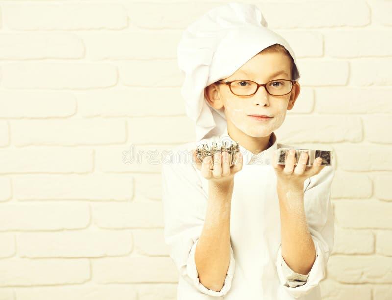 Pudrar den lilla gulliga kockkocken för den unga pojken i den vita likformign och hatten på nedfläckad framsida med exponeringsgl arkivfoto