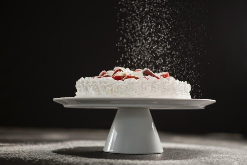 Pudrat socker som faller över den vita kakan på ställning royaltyfria bilder