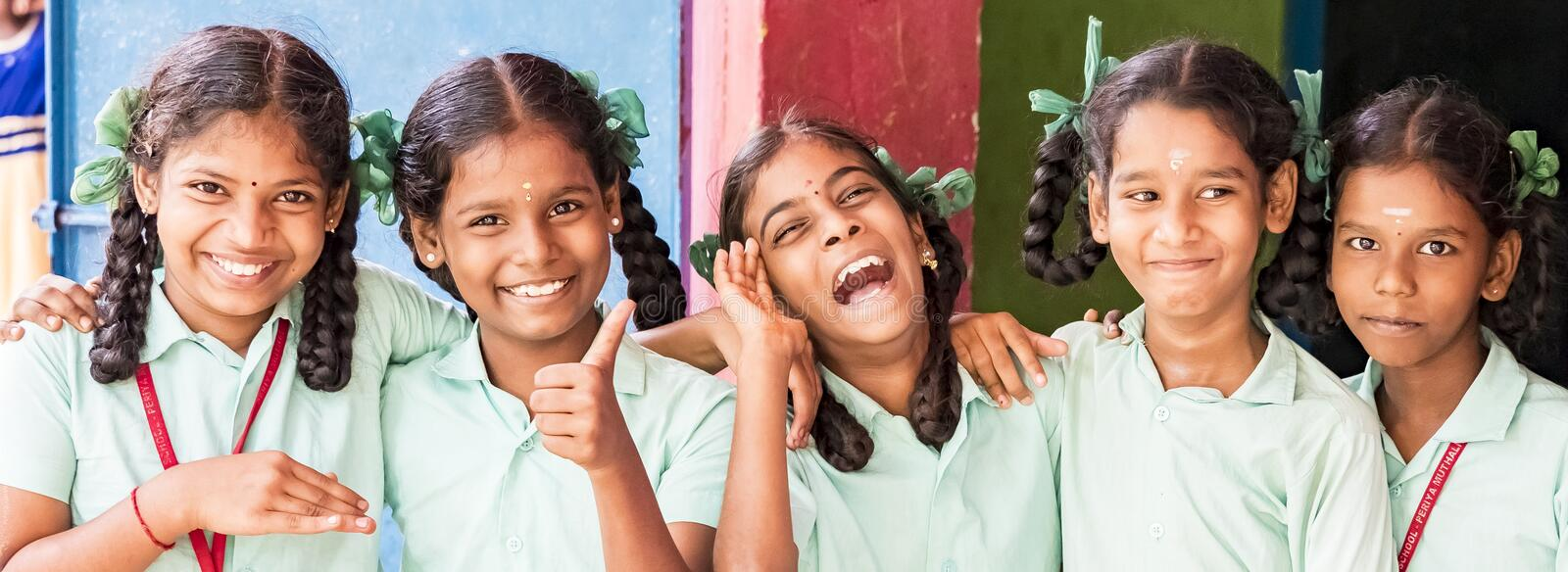 Best children friends girls classmates smiling laughing standing with hand on shoulder at the school. Multiethnic school kids royalty free stock photo