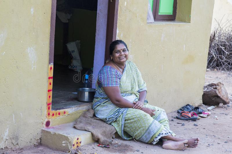 Indian woman sitting on the sidewalk in front of her house. PUDUCHERRY, PONDICHERY, TAMIL NADU, INDIA - SEPTEMBER CIRCA, 2017. An unidentified Indian woman stock image