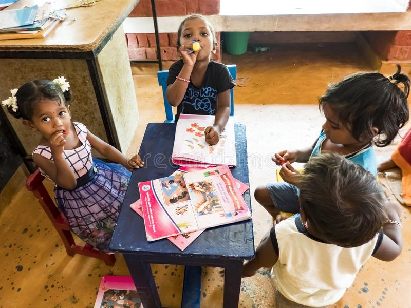Adorable poor little child, boys girls, sitting on chair at table, trying reading books. PUDUCHERY, INDIA - DECEMBER Circa, 2018. Unidentified adorable little royalty free stock image
