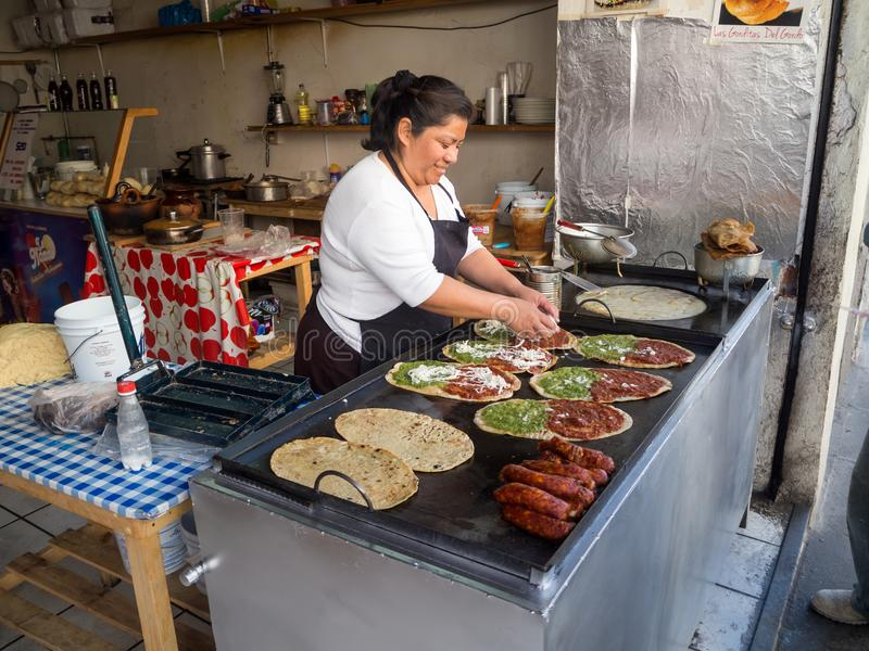 Puebla, Mexiko, Frau, die memelas, Tacos, Quesadillas, mexikanisches Straßenlebensmittel kocht lizenzfreie stockfotos