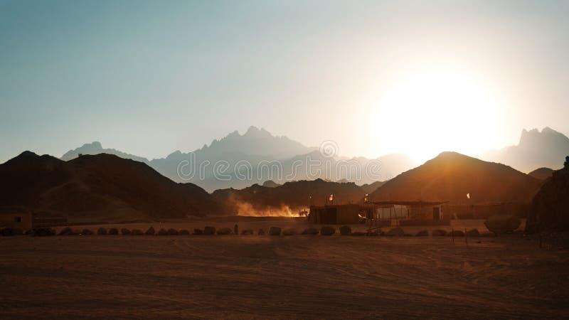Pueblo beduino en desierto en montañas en puesta del sol foto de archivo