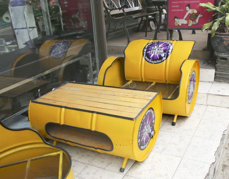 PUEBLO DE KARON, PHUKET, TAILANDIA - 24 DE JUNIO DE 2019: Las sillas y la tabla hicieron de bidones de aceite fuera de un café de fotografía de archivo libre de regalías