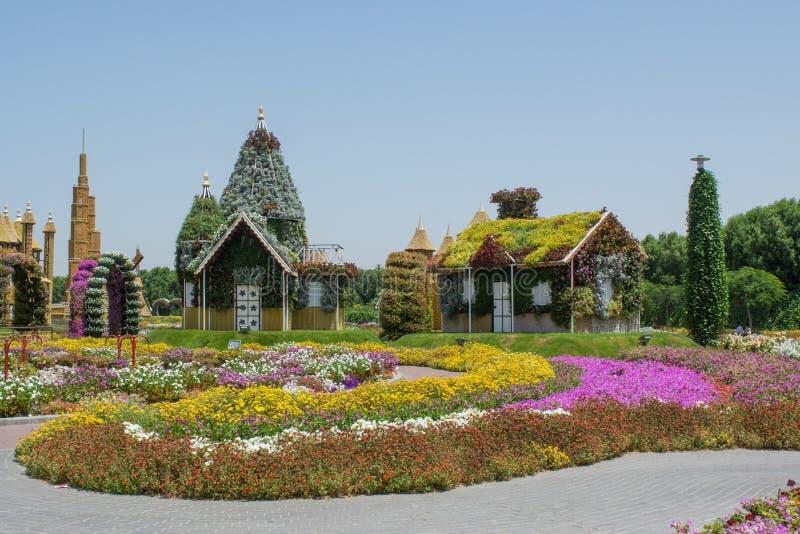 Pueblo de la fantasía con las casas y los castillos cerca de los macizos de flores coloridos imágenes de archivo libres de regalías