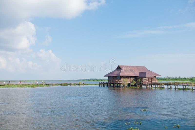 Pueblo de madera de la teca tradicional tailandesa en el lago tranquilo azul foto de archivo