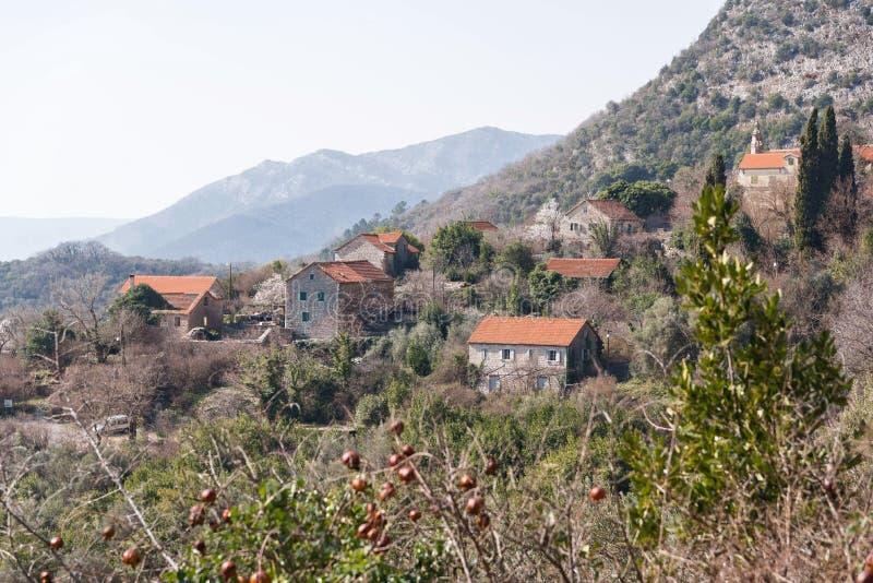 Pueblo de montaña viejo pintoresco en Montenegro Visión desde la colina a través de la corona de un árbol de granada Día asoleado foto de archivo libre de regalías
