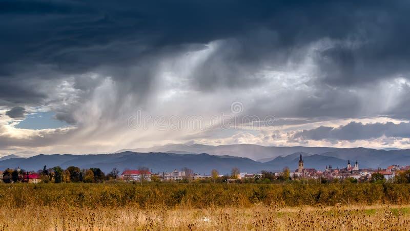 Pueblo de Transilvania con las montañas cárpatas en el fondo en tiempo del otoño, Rumania fotos de archivo