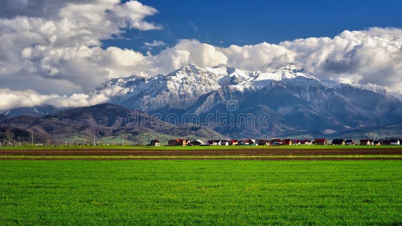 Pueblo de Transilvania en Rumania, en la primavera con las montañas en el fondo imagenes de archivo