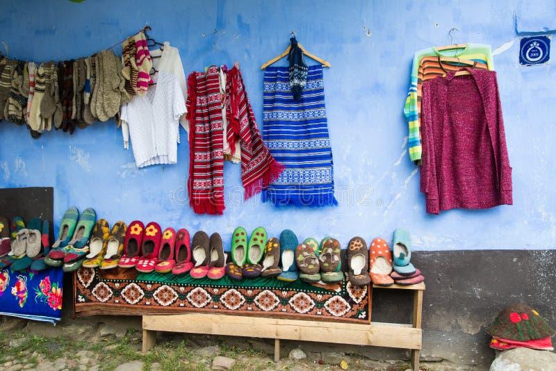 Pueblo de Viscri, Rumania - 17 de agosto de 2017: Calcetines de lana hechos a mano tradicionales y botines en venta en la calle d foto de archivo