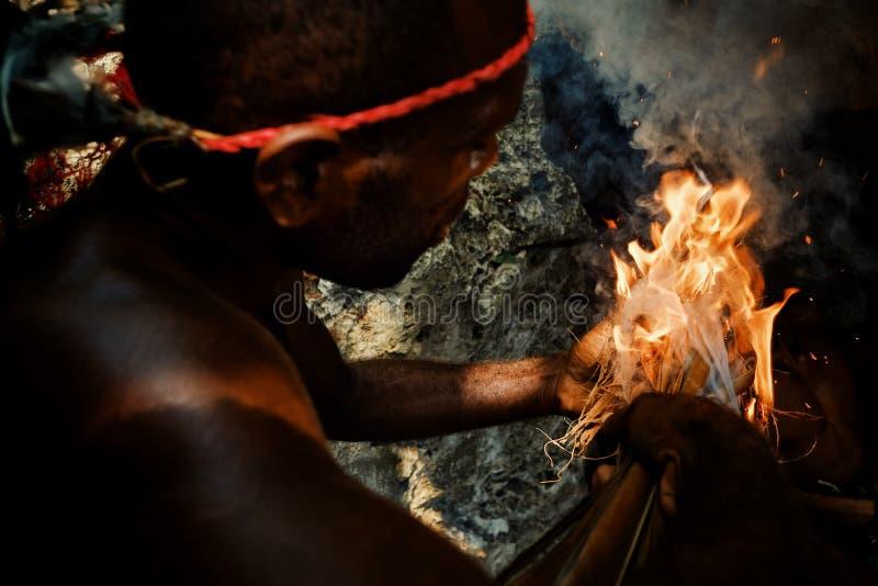 Pueblo de Walarano, isla de Malekula/Vanuatu - 9 DE JULIO DE 2016: hombre tribal local que sopla a un fuego para encenderlo en el fotos de archivo libres de regalías