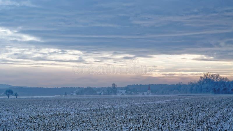 Pueblo del campo en colores del invierno por la nieve y la niebla imagenes de archivo