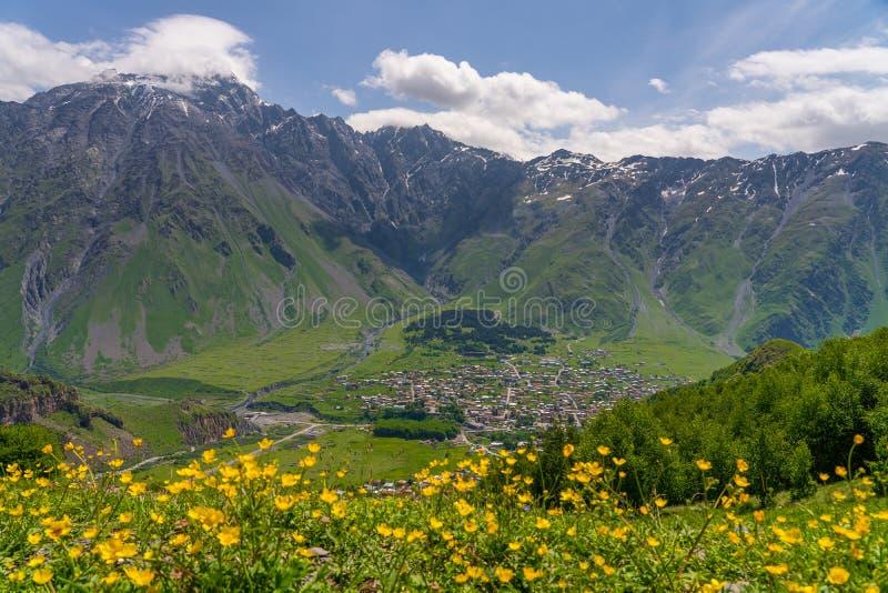 Pueblo en la estación de verano, pequeño pueblo de Kazbegi rodeado por la cordillera del Cáucaso en Georgia fotografía de archivo libre de regalías
