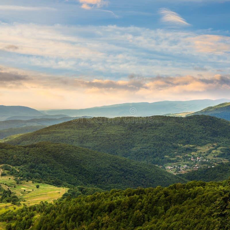 Pueblo en prado de la ladera con el bosque en montaña fotos de archivo