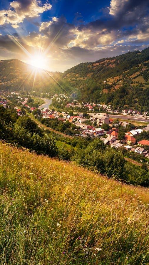 Pueblo en prado de la ladera con el bosque en montaña en el susnet fotos de archivo libres de regalías