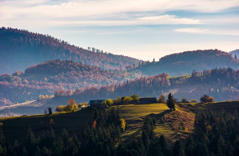 Pueblo encima de una loma herbosa en otoño imagenes de archivo