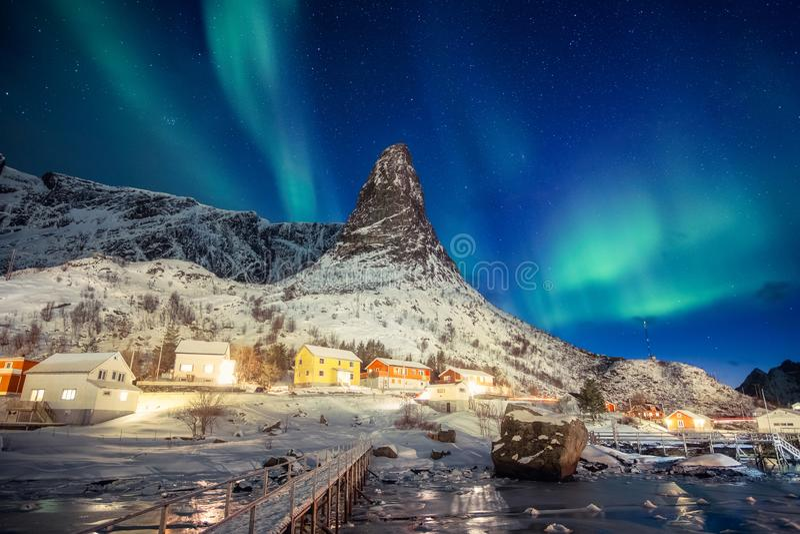 Pueblo escandinavo colorido con la aurora boreal sobre la montaña máxima en Lofoten fotos de archivo libres de regalías