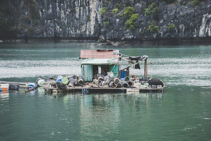 Pueblo flotante de Kuah p?lido en la bah?a de Halong en Vietnam Casas en el agua Costa rocosa fotos de archivo