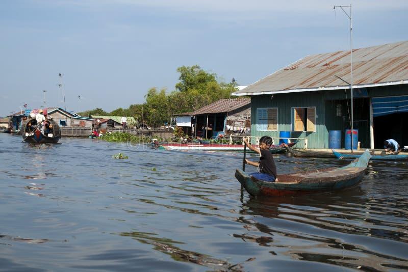 Pueblo flotante, muchacho en canoa que navega el tráfico del río imagenes de archivo