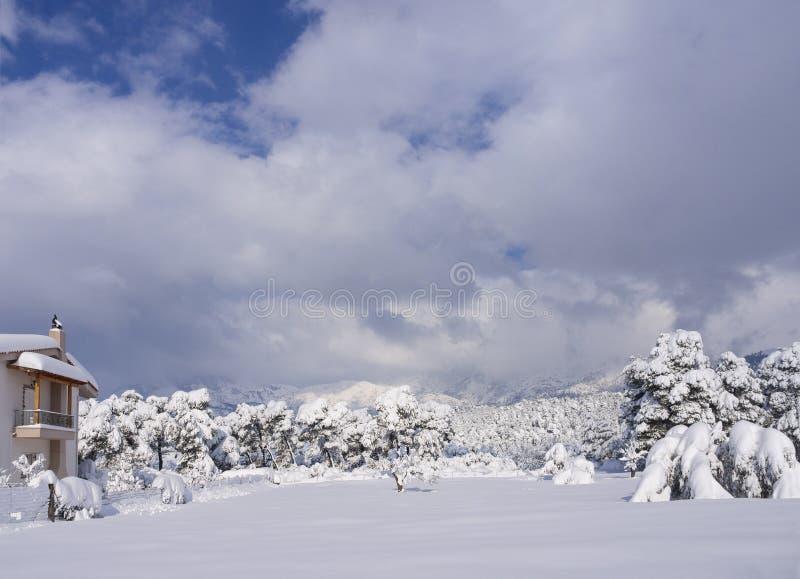 Pueblo griego y vista panorámica de la montaña nevada Dirfys y del cielo con las nubes en un día soleado en la isla de Evvoia, Gr foto de archivo