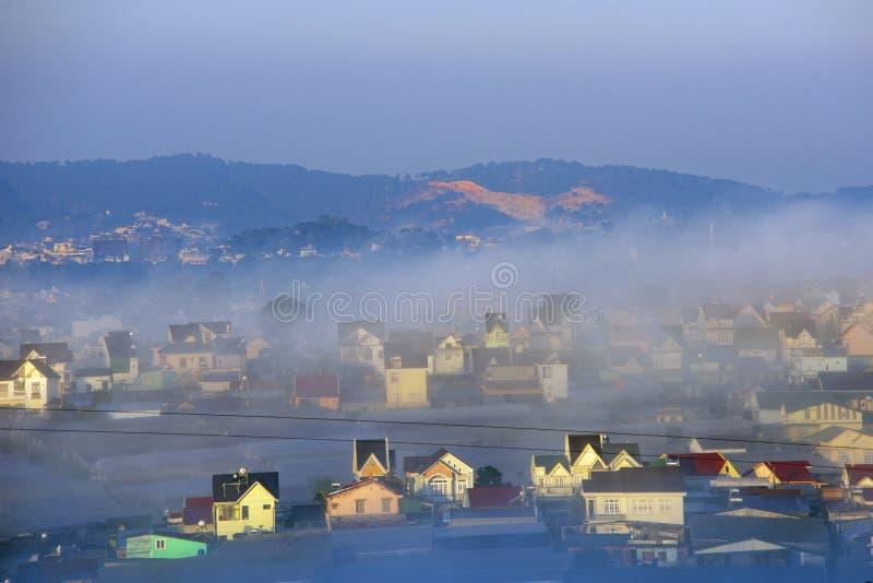 Pueblo hermoso de la cubierta de la niebla en valle con las casas coloridas como islas en la parte 7 de la niebla imágenes de archivo libres de regalías