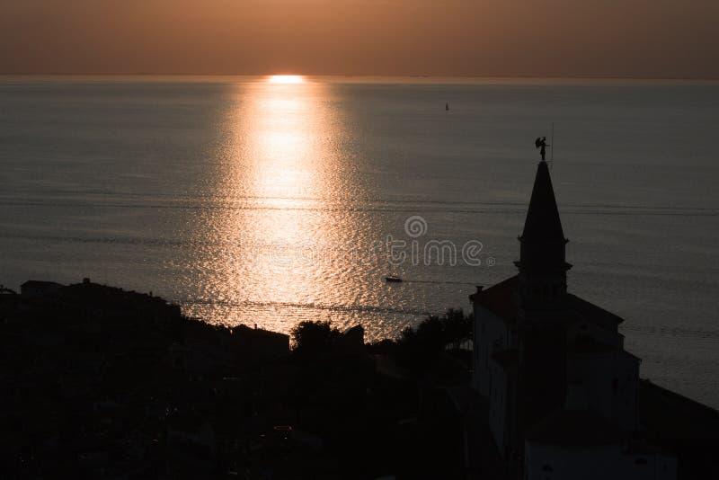 Pueblo hermoso de Piran en la costa costa del mar adriático en la silueta de la puesta del sol, Eslovenia imagen de archivo libre de regalías