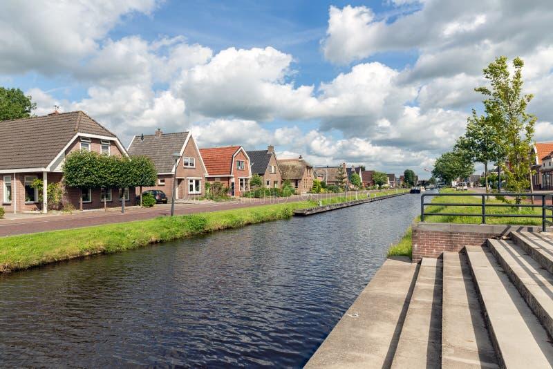 Pueblo holandés Appelscha en Frisia con las casas a lo largo de un canal imagenes de archivo