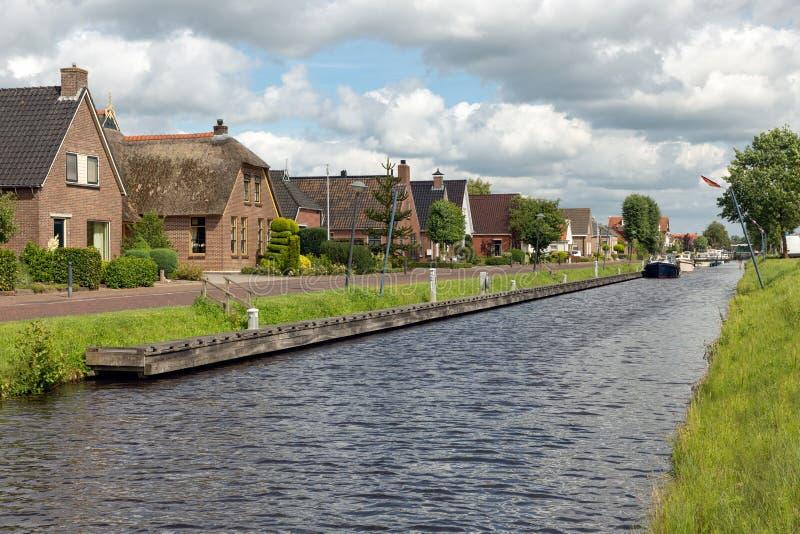 Pueblo holandés Appelscha en Frisia con las casas a lo largo de un canal fotos de archivo libres de regalías