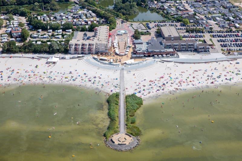 Pueblo holandés Makkum de la visión aérea con la playa y la gente de la natación imagen de archivo libre de regalías