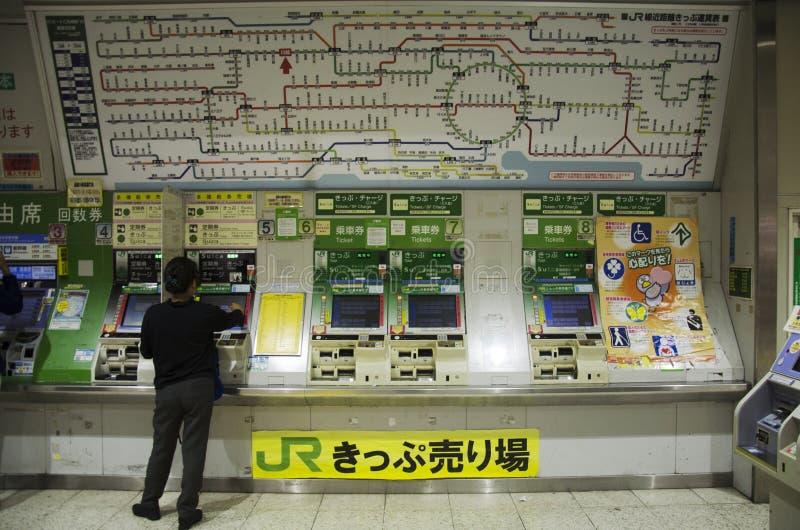 Pueblo japonés que compra boletos del tren de m que vende automático imagenes de archivo