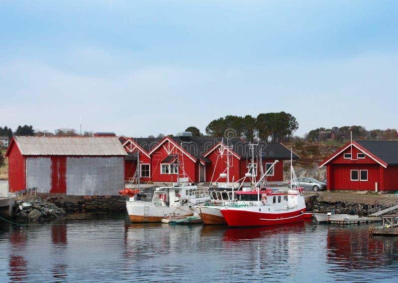 Pueblo pesquero noruego con las casas de madera rojas fotos de archivo