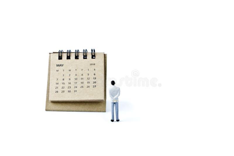 pueda Haga calendarios la hoja y al hombre plástico miniatura en el backgroun blanco foto de archivo
