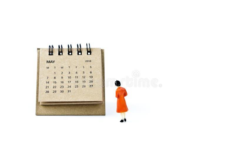 pueda Haga calendarios la hoja y a la mujer plástica miniatura en el backgro blanco fotos de archivo libres de regalías