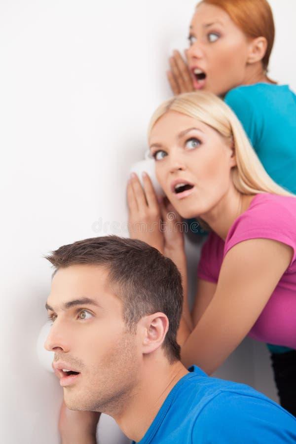 ¿Puede usted oír eso? Tres personas jovenes que escuchan detras de las puertas cerca del wal foto de archivo