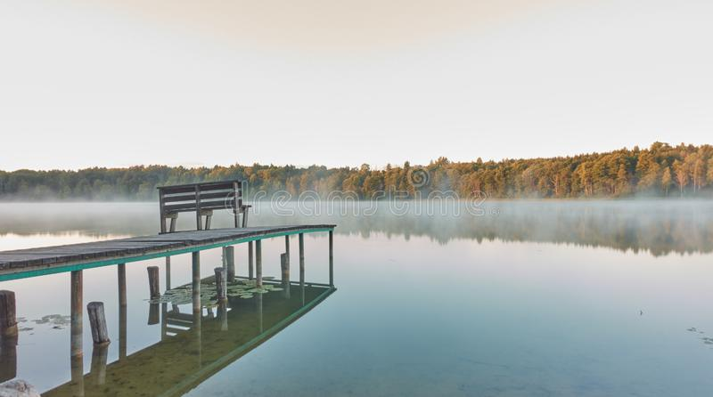 Puente al lago del bosque en la madrugada tranquila del verano fotografía de archivo libre de regalías