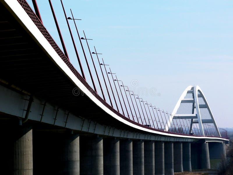 Puente arqueado de acero blanco elegante con las luces de calle inclinadas imágenes de archivo libres de regalías