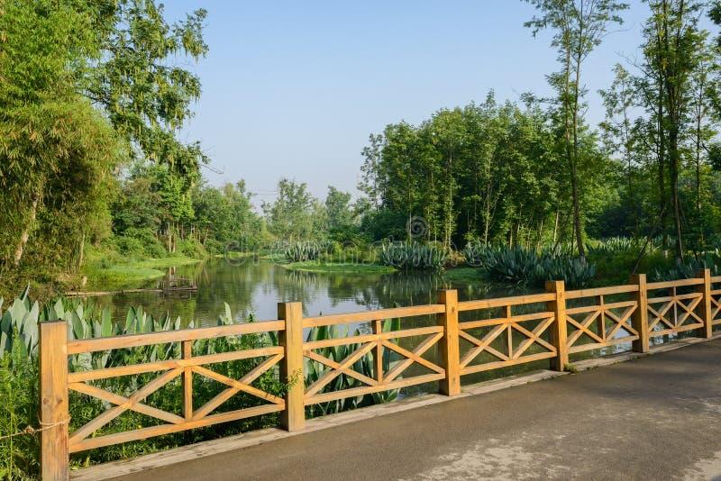 Puente balustraded de madera sobre el río por mañana soleada del verano imagen de archivo libre de regalías