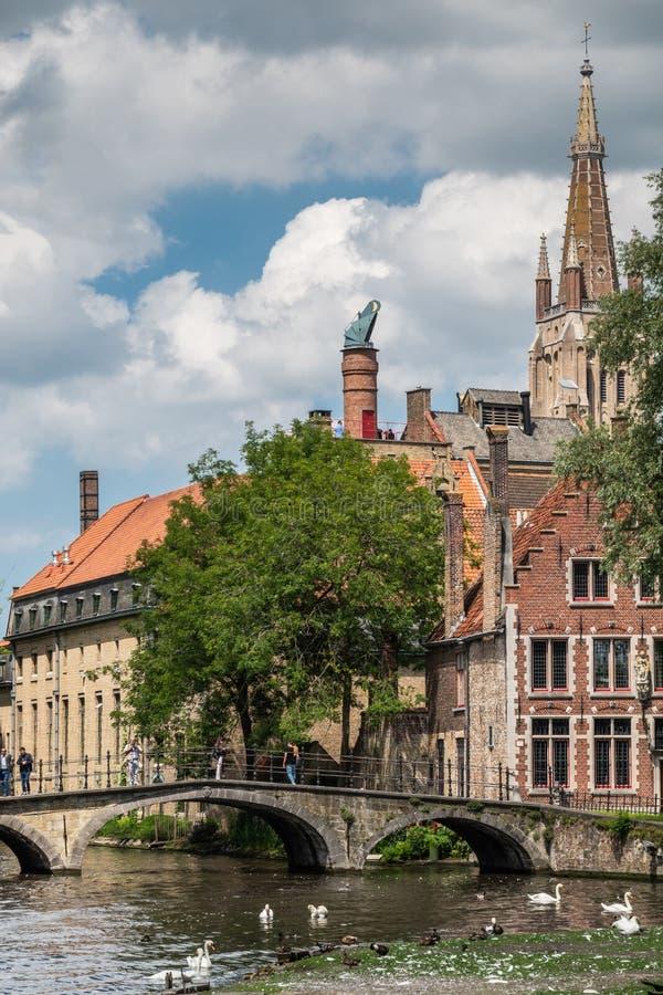 Puente a Beguinage con la torre de iglesia en Brujas, Flandes, Bélgica fotografía de archivo