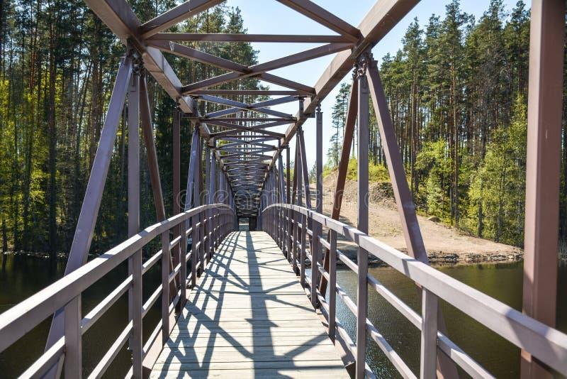 Puente a cielo abierto del metal a la iglesia en el río Vuoksa foto de archivo