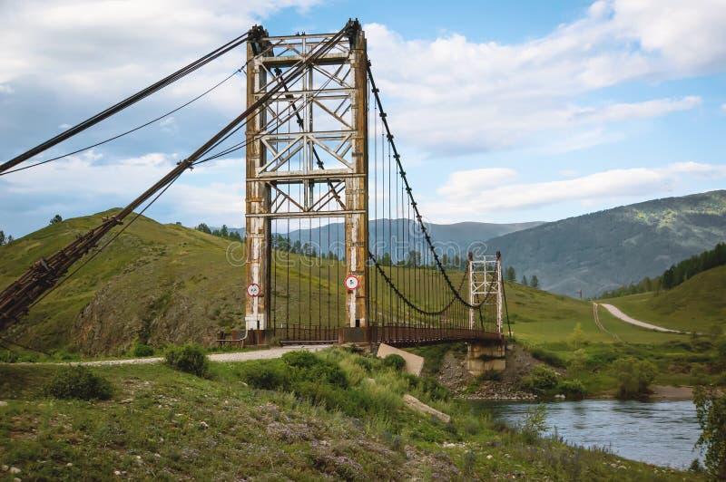 puente colgante de madera sobre un río de la montaña imagen de archivo