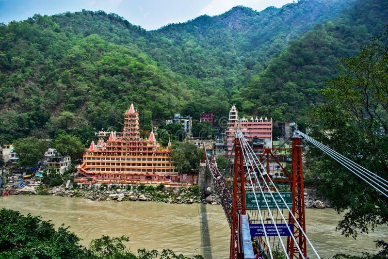 Puente colgante del jhula de Lakshman en Rishikesh con los barcos en el río del ganga haridwar y transportar en balsa imagenes de archivo
