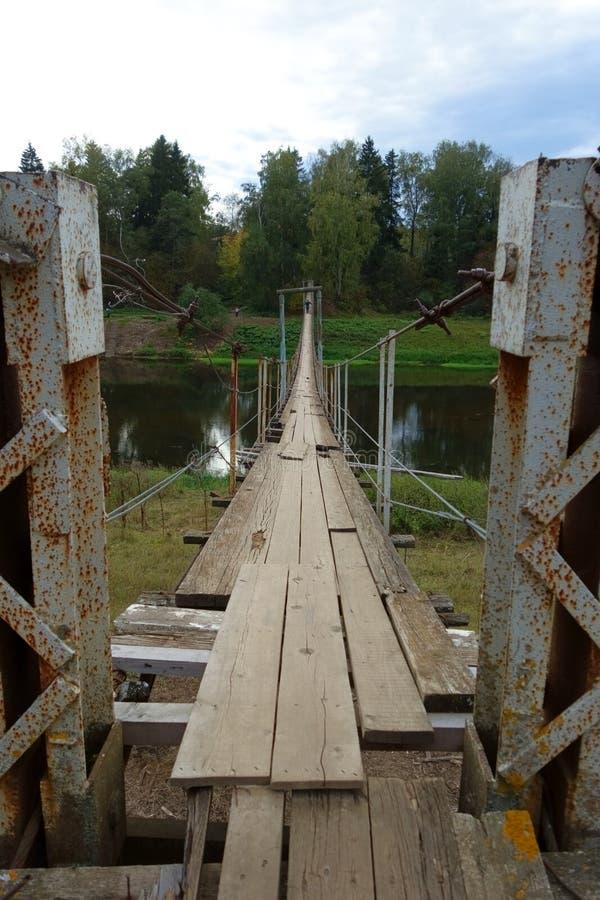 Puente colgante dilapidado peligroso viejo fotografía de archivo libre de regalías