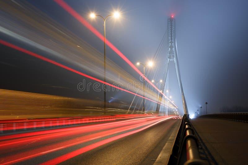 Puente colgante en niebla y las líneas de la velocidad imagenes de archivo