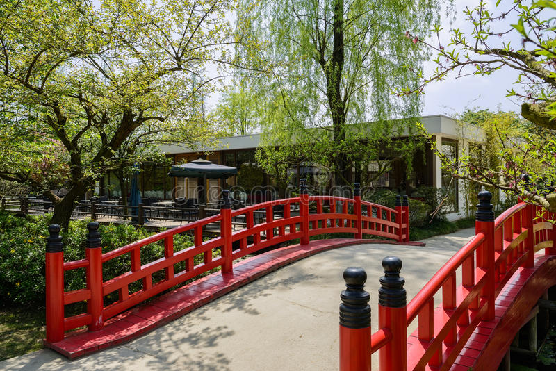 Puente con las barandillas de madera rojas antes del restaurante en árboles de fotografía de archivo libre de regalías